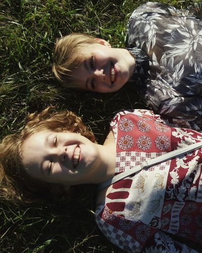 Portrait Of Smiling Friends Lying On Grass