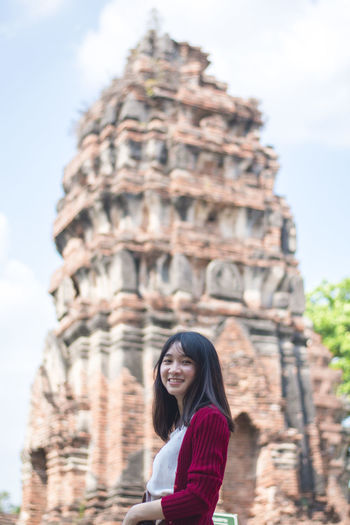 Portrait of smiling young woman standing in temple