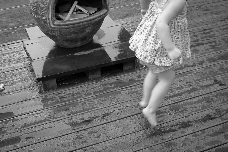 Girl jumping in rain on wooden floor