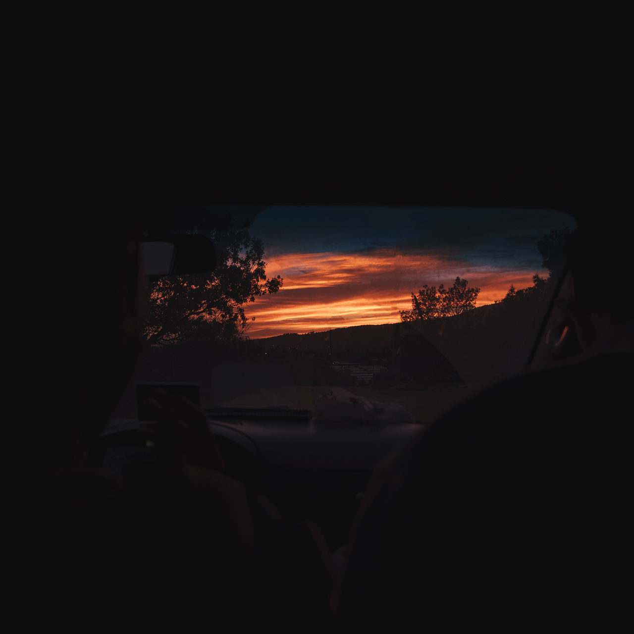 motor vehicle, car, mode of transportation, land vehicle, sky, transportation, sunset, vehicle interior, nature, car interior, no people, orange color, indoors, silhouette, night, copy space, beauty in nature, burning, dark, road trip