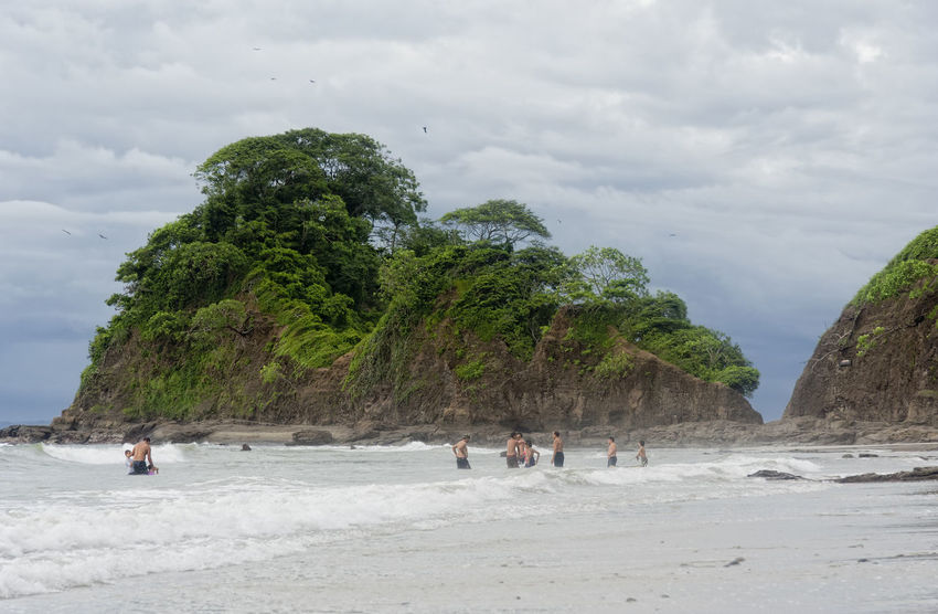 PUNTA LEONA, COSTA RICA - SEPTEMBER 6: People standing in sea at the beach in Punta Leona, Costa Rica. Punta Leona is a leading surfer hotspot with pristine beaches. Beach Life Beach Photography Been There. Costa Rica Nature Punta Leona Vacations Beach Beachphotography Beauty In Nature Cliff Lifestyles Medium Group Of People Nature Real People Rock - Object Sand Scenics Sea Summer Tree Water
