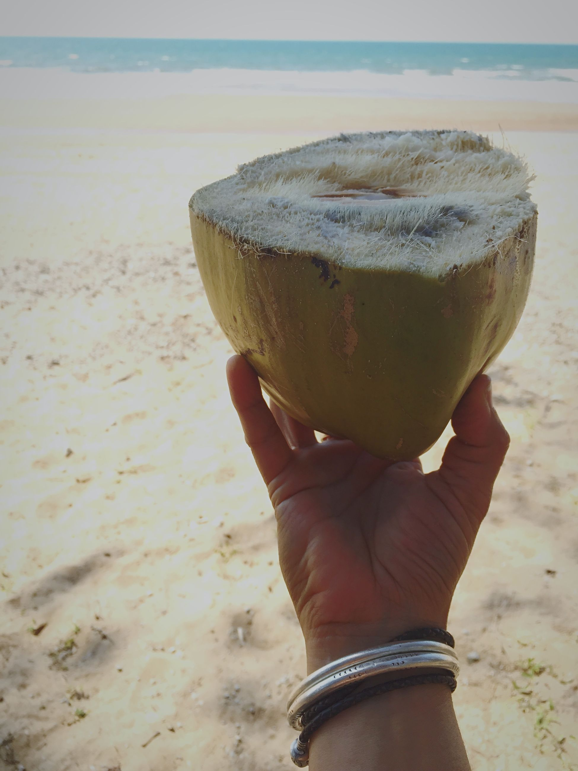 drink, food and drink, beach, refreshment, close-up, focus on foreground, holding, sand, shore, sea, freshness, lifestyles, water, outdoors, part of, sky, person