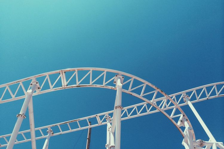 Low angle view of white rollercoaster against clear blue sky