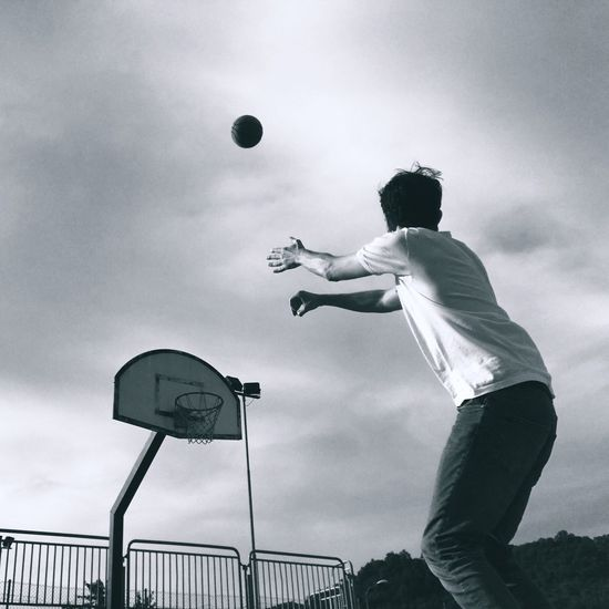 Low angle view of man playing basketball at court