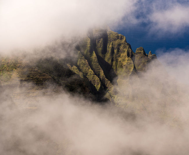 Fluted rocks of the na pali mountains through clouds from pihea trail near pu'u o kila lookout kauai