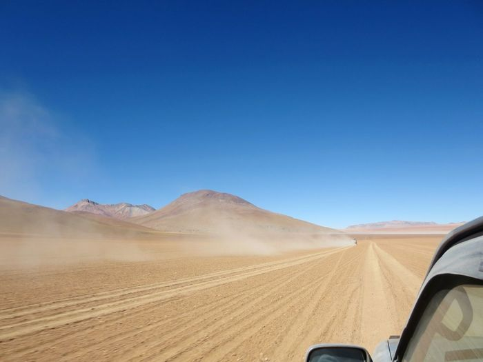 Cropped image of car on dirt road at desert