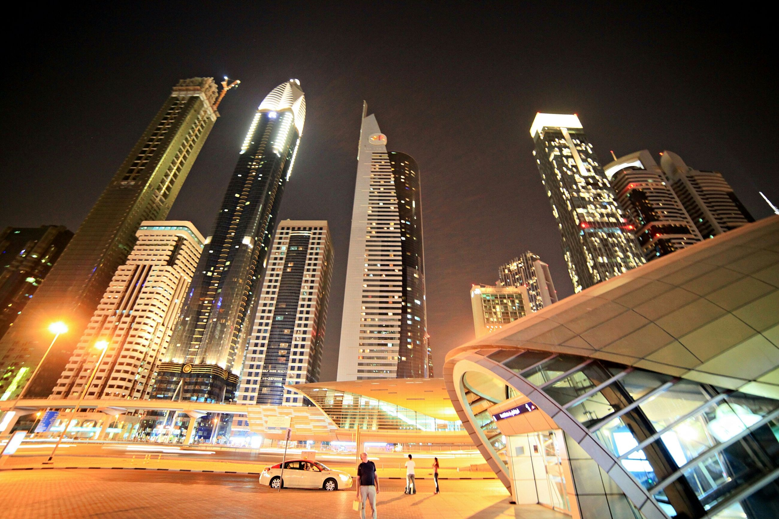building exterior, architecture, skyscraper, built structure, city, modern, tall - high, office building, tower, illuminated, capital cities, financial district, city life, night, urban skyline, low angle view, travel destinations, cityscape, building, downtown district