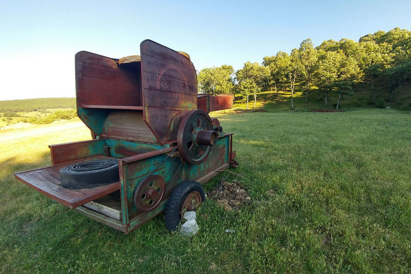 Haymaker Abandoned Cannon Day Environment Field Grass Green Color Growth History Land Landscape Metal Nature No People Old Outdoors Plant Rusty Sky The Past Tree Wheel