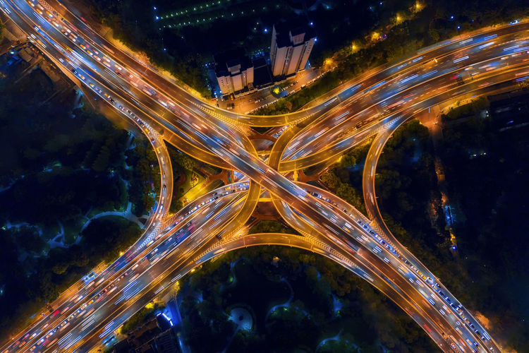 Aerial view of highway junctions shape letter x cross at night. Bridges, roads, or streets in connection or transportation concept. Structure of architecture in urban city, Shanghai Downtown, China. Shanghai China City Road Downtown District Financial District  Architecture Landmark Landscape Building Highway Expressway Night Illuminated Motion No People Building Exterior Built Structure Long Exposure Light Trail Glowing Speed Nature Blurred Motion Transportation Abstract Street Cityscape Outdoors