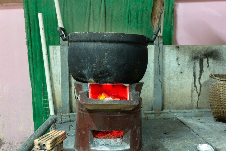 Cooking aluminum pot boiling on charcoal burning stove. Heat - Temperature Burning Fire Flame Fire - Natural Phenomenon Container No People Preparation  Wood - Material Wall - Building Feature Nature Indoors  Wood Burning Stove Household Equipment Appliance Wood Log Glowing Metal Day