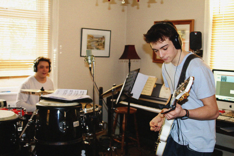 Young Men Playing Music While Practicing At Home