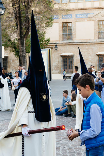 Easter nazarenes in white robes with black hoods during procession holding big candle, they are members of a brotherhood in the Holy Week in Cordoba. Andalusia Andalusian Cofradia Córdoba Easter Holy Week Holy Week Celebrations SPAIN Spanish Tourist Attraction  Tradition Travel Brotherhood Culture Culture And Tradition Day Holy Week Tradition Nazarene Outdoors Parade Procession Real People Religion Religious  Tourism