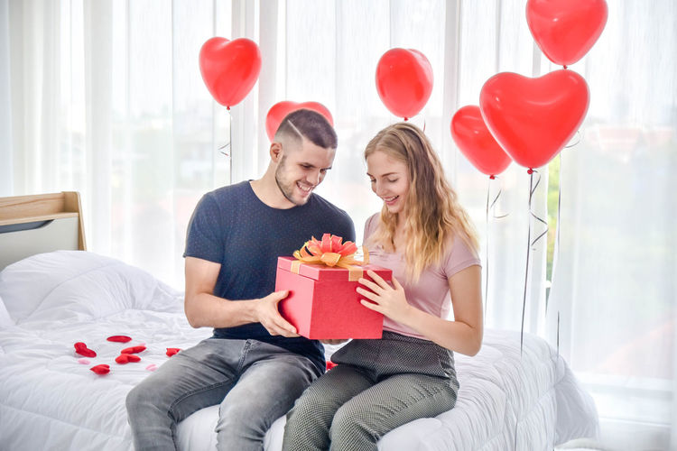 Young couple holding balloons in box