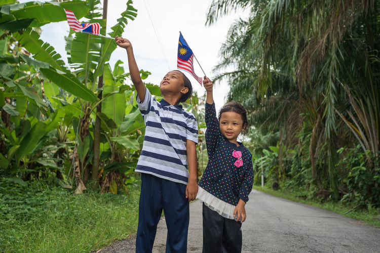 Two adorable kids flying Malaysia flag in nature background. Selective focus. Malaysia Independence Day concept. Happiness Patriotic Patriotism Boys Casual Clothing Child Childhood Day Family Females Front View Girls Happiness Independence Day Innocence Malaysia Males  Men Merdeka Outdoors Plant Positive Emotion Sibling Sister Standing Three Quarter Length Togetherness Two People Women