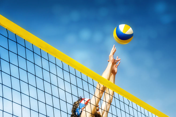 Beachvolley ball player jumps on the net and tries to blocks the ball Ball Beach Volleyball Day Leisure Activity Lifestyles Low Angle View Men Net - Sports Equipment One Person Outdoors People Playing Real People Sky Sport Sportsman Volleyball - Sport Young Adult