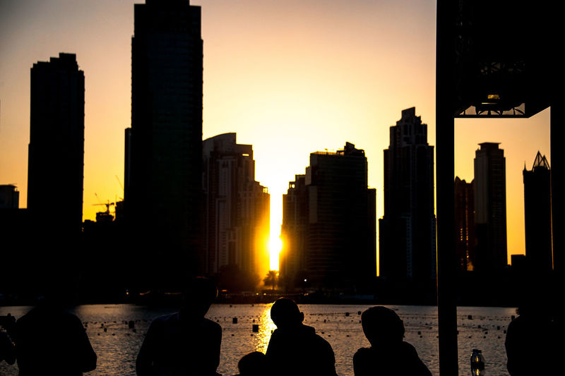 Folks gathering together to take in a splendid sunset Architecture Building Building Exterior Built Structure City Cityscape Group Of People Modern Office Building Exterior Orange Color Silhouette Sky Skyscraper Sunset Tall - High Tower Travel Destinations