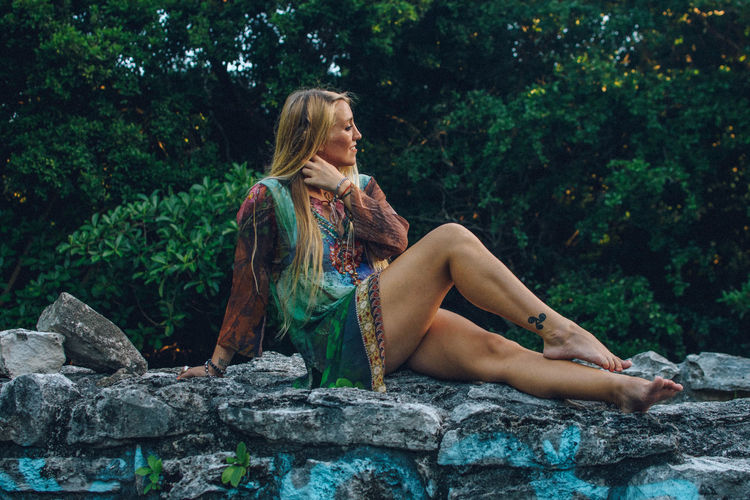 Full length of woman sitting on stone wall outdoors