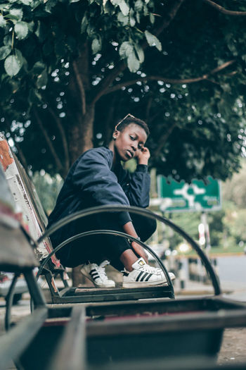 Street wear EyeEm EyeEm Best Shots Fresh On Market 2018 Shoe Streetphotography Africa Teenager Portrait Woman Adult People Arts Culture And Entertainment One Person Young Adult Sitting Women Outdoors Fashion Road Day Tree Lifestyles One Young Woman Only