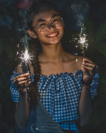 Portrait of young woman holding sparkler at night