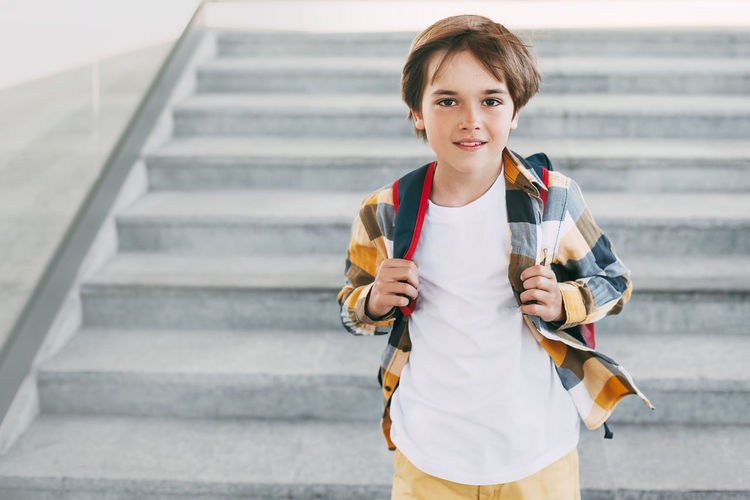 Portrait of boy holding umbrella on staircase