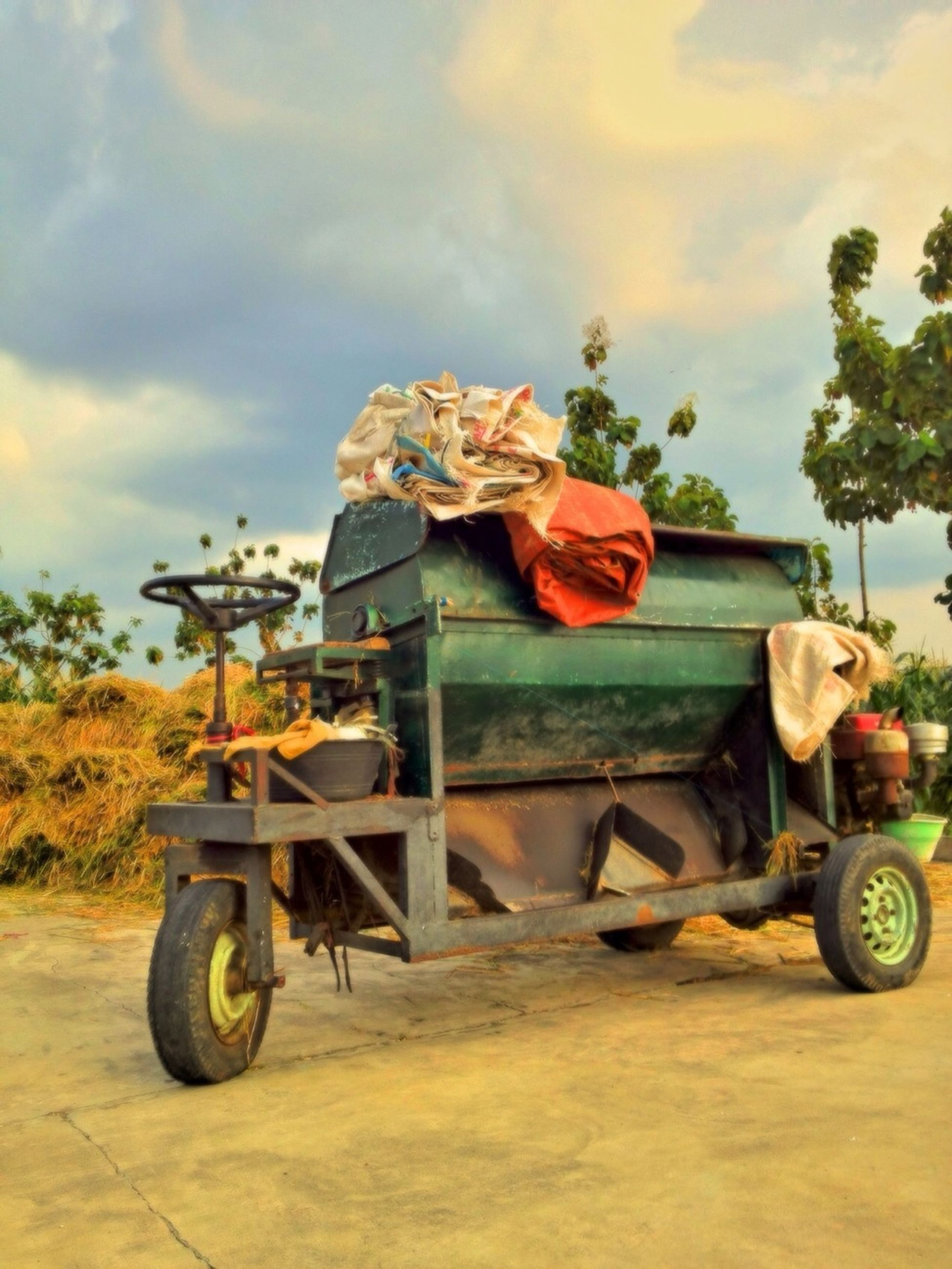 sky, mode of transport, land vehicle, cloud - sky, transportation, cloud, tractor, day, outdoors, tree, sunlight, toy, sand, cloudy, abandoned, stationary, childhood, cart