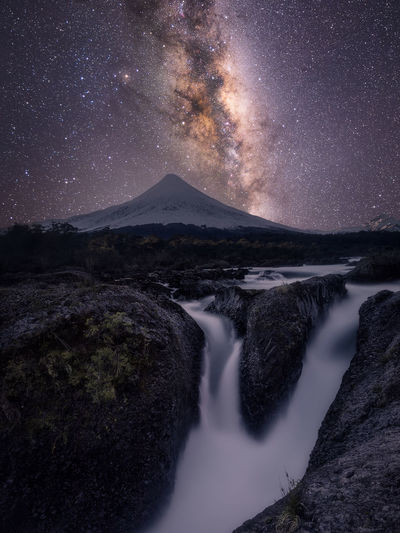 Scenic View Of Waterfall By Mountains Against Star Field At Night