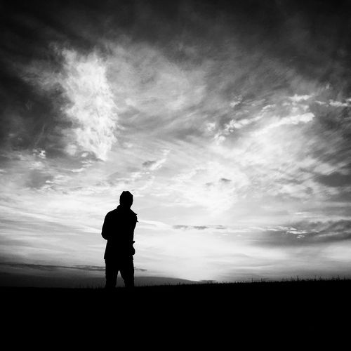 Rear view of silhouette man on field against cloudy sky