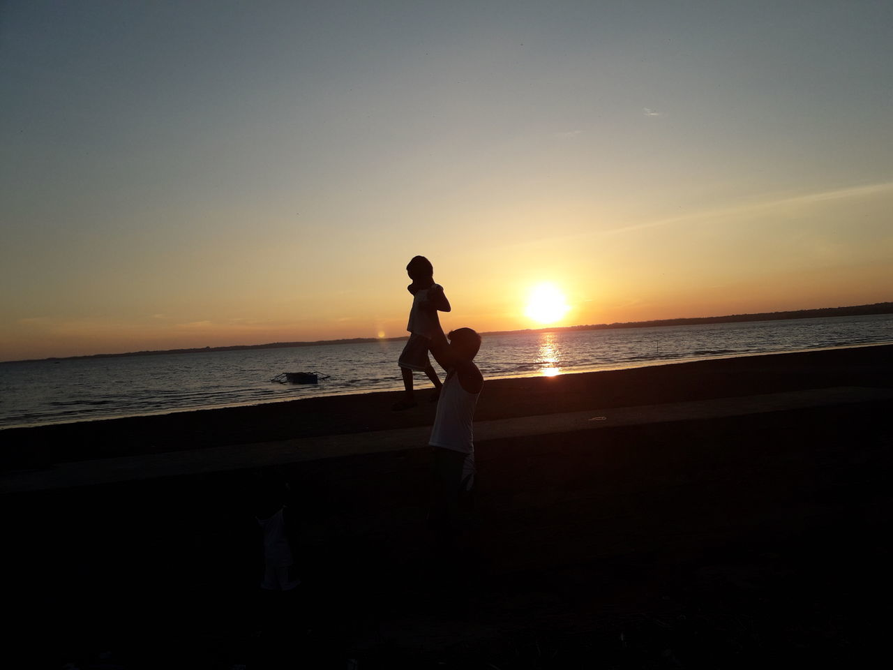 sunset, sea, beach, water, horizon over water, silhouette, scenics, nature, beauty in nature, two people, sun, side view, full length, standing, tranquility, tranquil scene, sky, leisure activity, sand, real people, vacations, outdoors, men, day, people