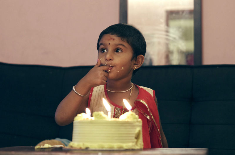 Girl eating birthday cake while sitting at home