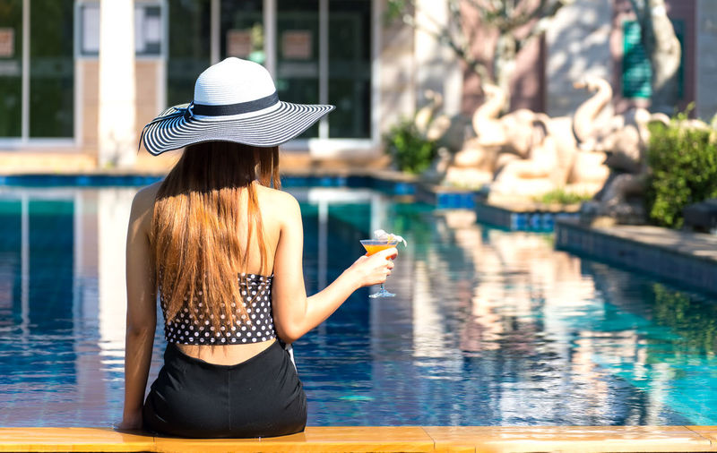 Rear view of woman wearing hat while standing by swimming pool