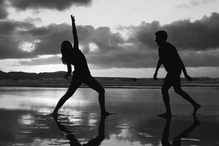 Silhouette men standing on beach against sky