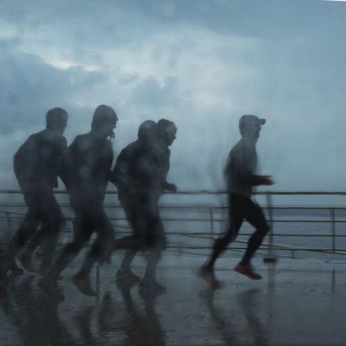 Silhouette people walking on wet road against sky