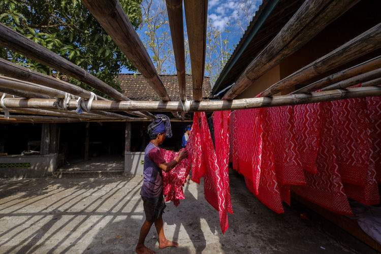 A man is preparing to hang fabric for drying One Person Red Clothing Lifestyles Traditional Clothing Nature Outdoors Work Batik Drying Travel Destinations Tourism Industry Batik Maker Hand Made People Klaten, Jawa Tengah Indonesia_photography Java Asian  Asian People