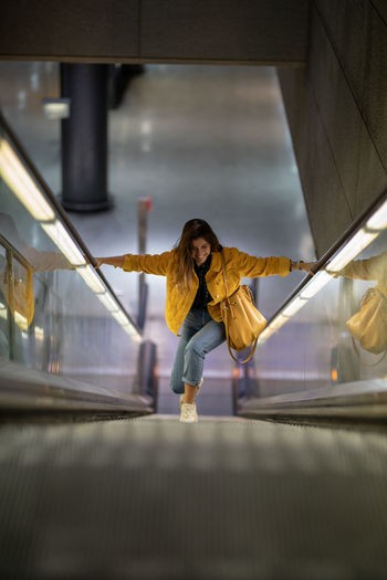 High Angle View Of Young Woman On Escalator
