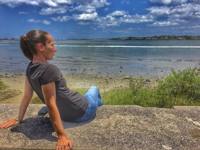 Young woman sitting on retaining wall against sea