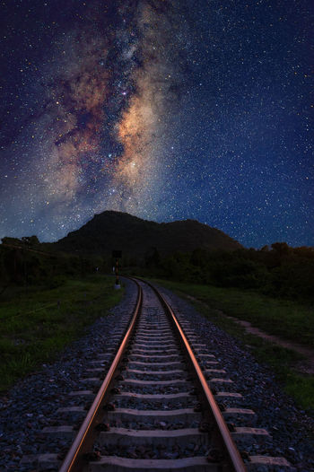 Diminishing perspective of railroad track against star field at night