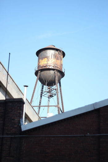 Low angle view of water tower on building against clear sky