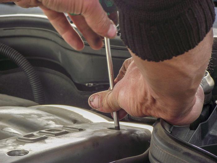 Cropped hands of mechanic repairing car