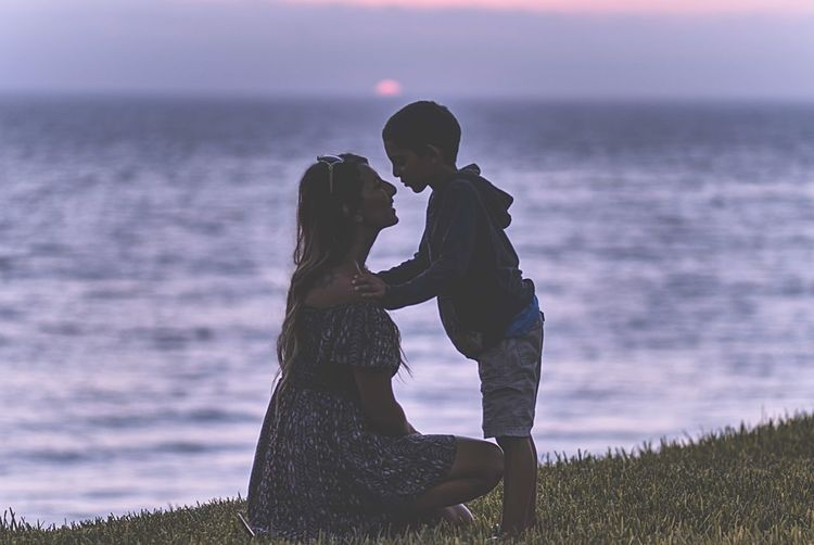 Side View Of Mother And Son On Grassy Shore During Sunset