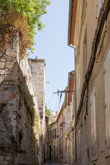 A narrow street at Arles, France Architecture Branch Building Exterior Built Structure City Construction Day Development Low Angle View No People Old Town Outdoors Sky Stone Material Tall - High Tourism Town Travel Destinations