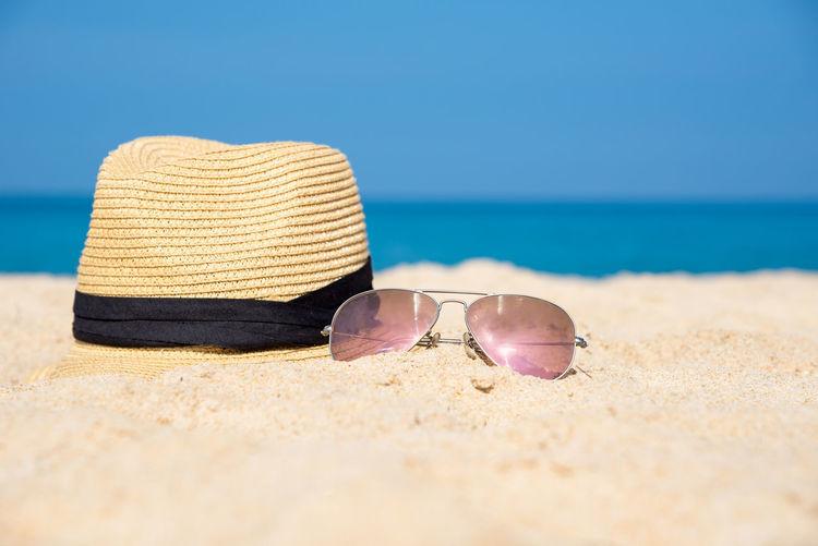Surface level of sunglasses on beach against sky