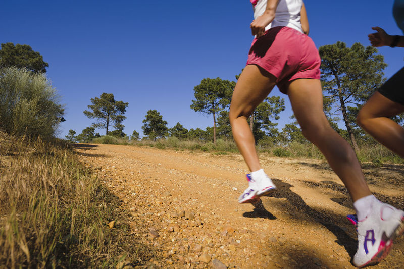 Low section of woman running on land against sky