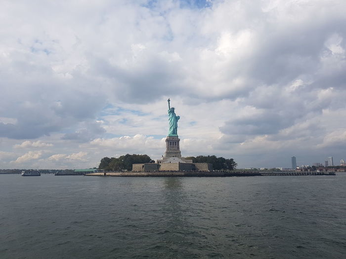 Statue of liberty by sea against cloudy sky