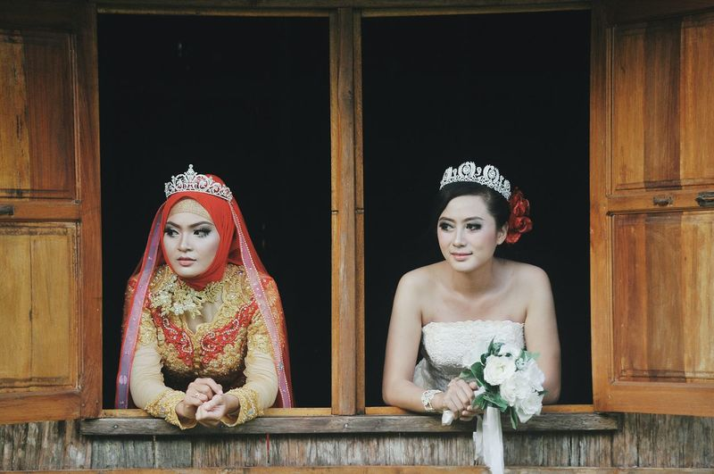 Brides wearing wedding dress while looking through windows