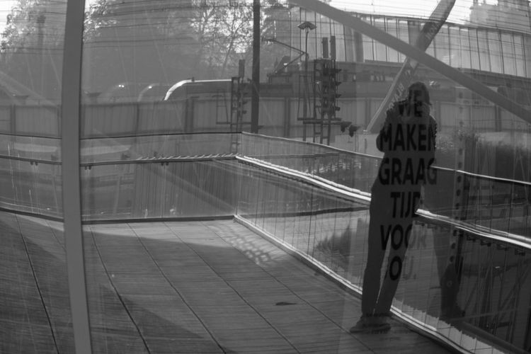 Man seen through railing bridge