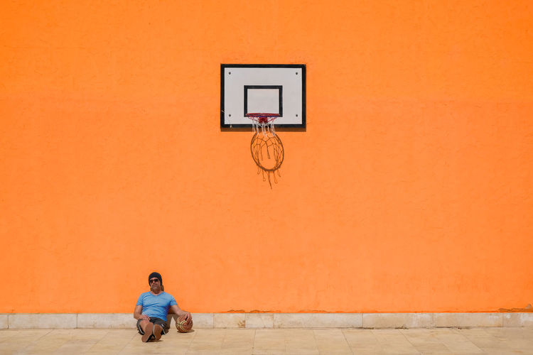 EyeEmNewHere Basketball - Sport One Person Sport Basketball Hoop Wall - Building Feature Leisure Activity Copy Space Orange Color Sitting Architecture Lifestyles Adult Full Length Day Outdoors Casual Clothing Men Motion Basketball - Ball Copy Space Resting Waiting Skill  Competitive Sport 17.62° My Best Photo