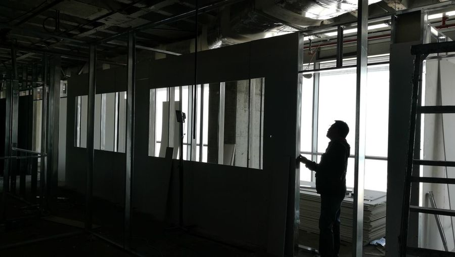 EyeEmNewHere silhouette photography Interrior office construction Man Working Indoors  Full Length One Person Interior Decoration Architectural Feature Winter Morning Daytime Photography