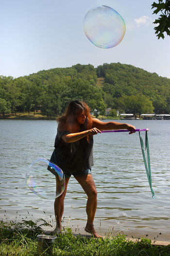 Beauty In Nature Blue Brunette Woman Bubbles Bubbles And Water Bubbles... Bubbles...Bubbles.... Casual Clothing Enjoyment Full Length Lake Legs Leisure Activity Lifestyles Mountain Nature Outdoors Scenics Shoreline Sunlight Tranquil Scene Tranquility Tree Vacations Water Woman Making Bubble