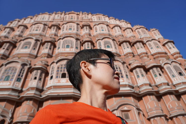 Low angle portrait of young man wearing sunglasses against sky