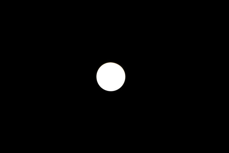 Low angle view of moon against dark sky